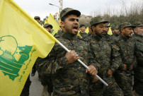 """In this picture taken on Friday, Feb. 14, 2014, Hezbollah fighters march in a parade during the memorial of their slain leader Sheik Abbas al-Mousawi, who was killed by an Israeli airstrike in 1992, in Tefahta village, south Lebanon. Hezbollah says Israel carried out an airstrike targeting its positions in Lebanon near the border with Syria earlier this week, claiming it caused damage but no casualties. Hezbollah said the attack was near the eastern Lebanese village of Janta. It vowed to retaliate but said it will """"choose the appropriate time and place."""" (AP Photo/Mohammed Zaatari)"""
